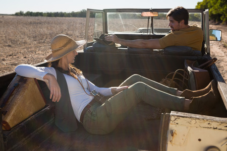 Young woman resting with man driving off road vehicle at forest Lizenzfreie Bilder
