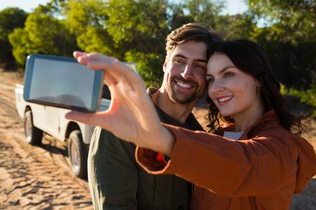 Happy beautiful woman with man taking selfie on field