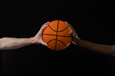 Close-up competitors holding basketball against black background