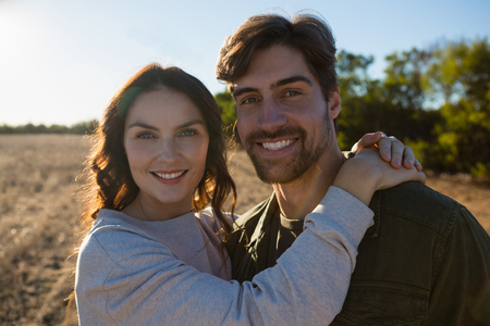 Portrait of smiling young couple standing on landscape