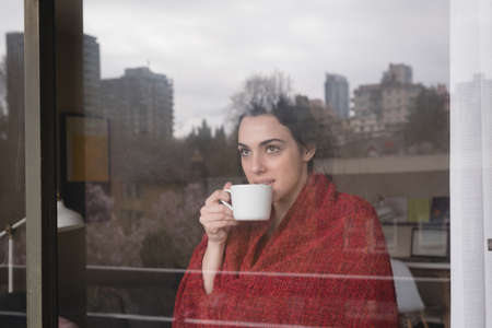 contemplated: Contemplated woman with coffee cup seen through glass window LANG_EVOIMAGES