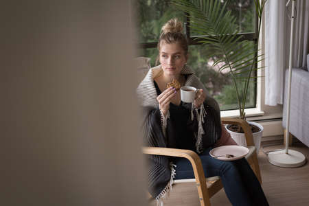 contemplated: Thoughtful woman having breakfast while sitting on chair by window at home