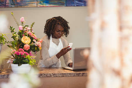 floristry: Female florist using laptop and mobile phone in flower shop