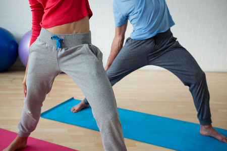 Low section of male instructor exercising with female student in health club Stock Photo