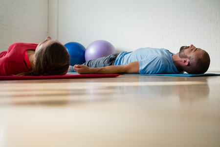 Instructor and student exercising while lying on mat in yoga studio