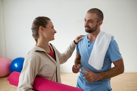 Female student holding exercise mat interacting with instructor in health club Banco de Imagens