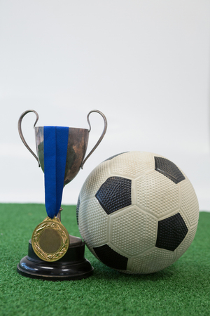 Close-up of football, trophy and medal on artificial grass against white background Stock Photo