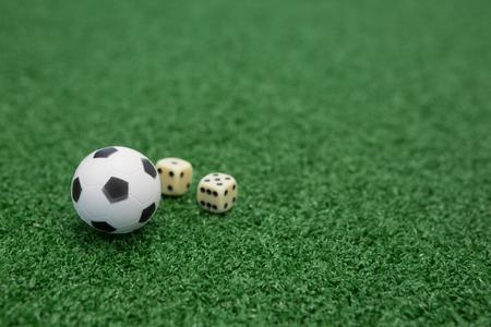 サッカーと人工芝生の上のサイコロのクローズ アップ