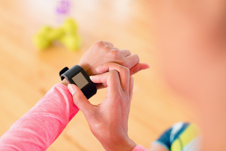 Close-up of woman using smartwatch in the gym