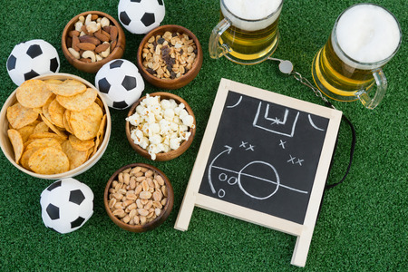 Close-up of strategy board, football and snacks on artificial grass Фото со стока