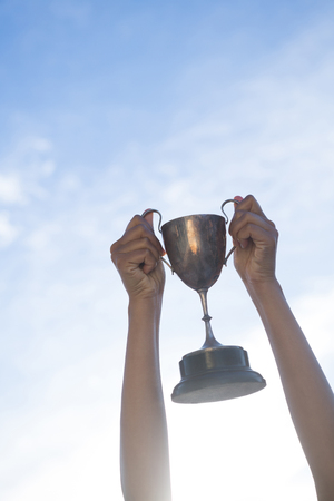 Close-up of hand holding a trophy against sky and cloud