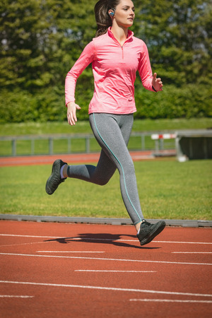 Young woman jogging on a race track