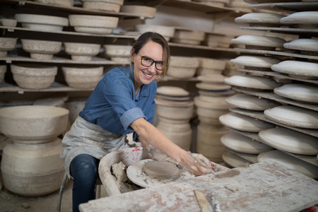 Portrait of female potter molding a clay in pottery workshop Stock Photo