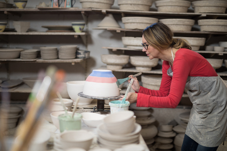 Female potter painting bowl in pottery workshop
