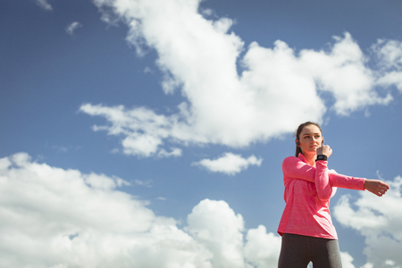 Young woman performing stretching exercise on a sunny day