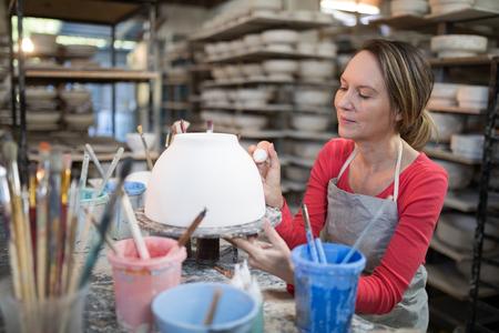 Female potter decorating bowl in pottery workshop