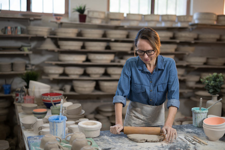 Female potter flattening the clay with rolling pin in workshop Stock Photo