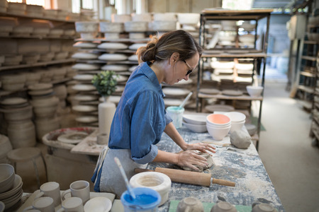 Female potter molding a clay in pottery workshop Reklamní fotografie - 87764507