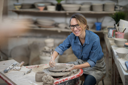 Portrait of female potter molding plate with hand tool in pottery workshop Stock Photo