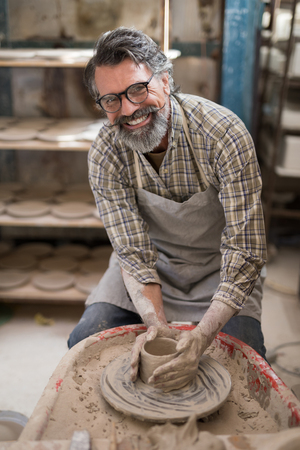 seller: Portrait of male potter molding a clay in pottery workshop