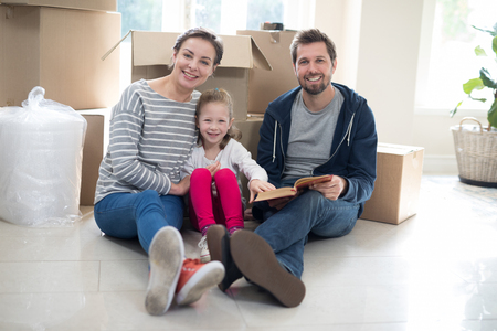 Parents and daughter reading books in living room at home
