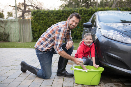 Portrait of teenage girl and father washing a car on a sunny day Stock Photo