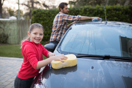 Teenage girl and father washing a car on a sunny day