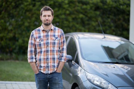 Portrait of man standing near the car