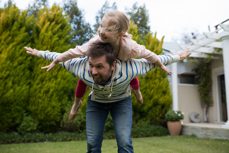 Young girl rides piggyback on her fathers shoulders in the park Stock Photo