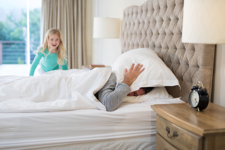 nightwear: Father and daughter having fun on bed at home