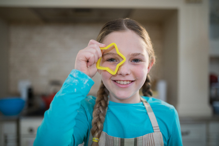 Girl holding cookie cutter on her eyes in kitchen