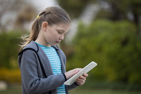Young girl using digital tablet in the park