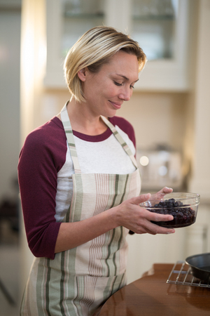 domicile: Smiling woman holding bowl of dried blue berries in kitchen at home