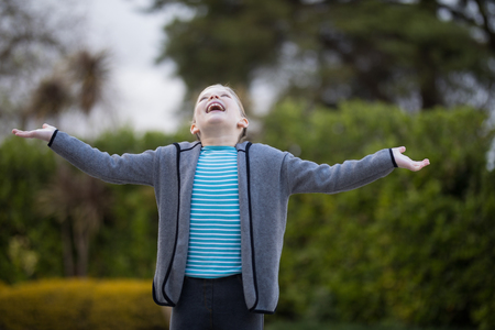 Young girl standing in the park with arms wide open