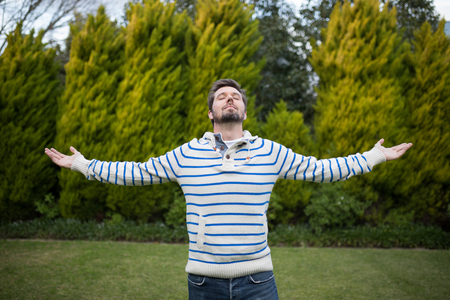 Man standing with arms wide open in the park