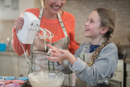 blender: Smiling mother and daughter mixing eggs and wheat flour in a bowl at kitchen