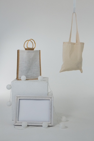 Bags And Picture Frame Decorated With Lights On White Background ...