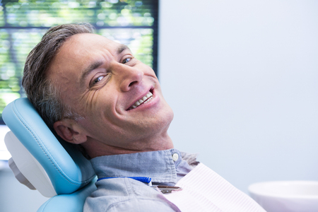 Portrait of smiling man sitting on chair at dentist clinic Stock Photo