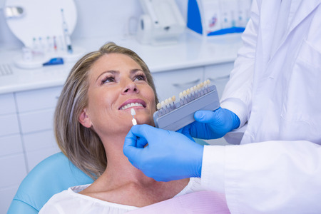 Hoge hoekmening van tand die van de artsenholding materiaal door patiënt kliniek witten Stockfoto - 87769022