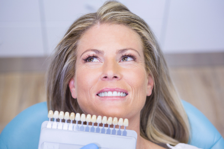 Extreme close up doctor holding tooth whitening equipment by smiling patient at medical clinic