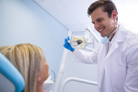 Low angle view of dentist adjusting lamp while looking at patient in medical clinic Stock Photo