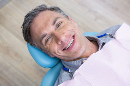 Overhead portrait of smiling man sitting on chair at dentist clinic
