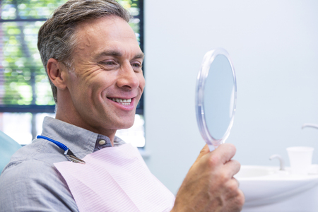 Portrait of smiling man looking in mirror at dental clinic Stock Photo