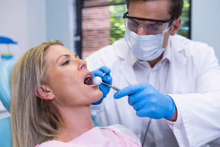 Close-up of doctor wearing surgical mask examining patient at dental clinic Stock Photo