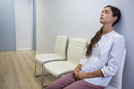 Sad patient with eyes closed sitting on chair in waiting room at hospital