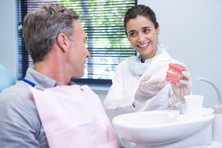 Happy dentist showing dental mold to man at clinic