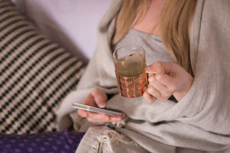 domicile: Mid section of woman with drink using mobile phone on sofa at home