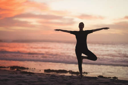 Pregnant woman performing yoga on the beach at dusk