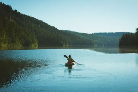 Rear view of man kayaking in river on a sunny day