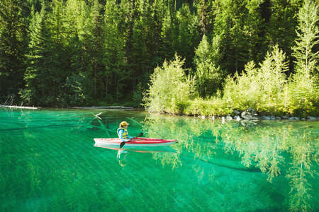 Person kayaking in river on a sunny day LANG_EVOIMAGES
